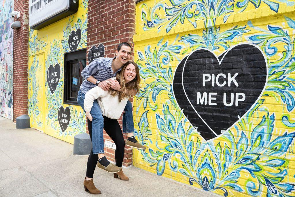engaged couple clowning around in front of mural