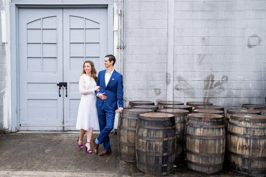 bride and groom hug in front of beer barrels