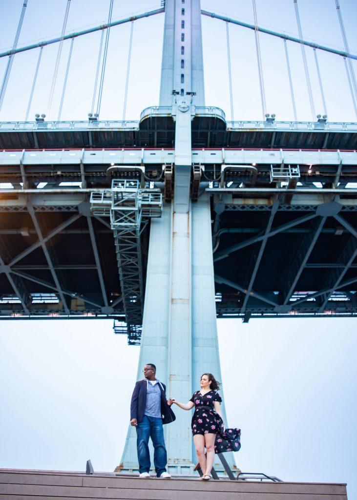 engaged couple hold hands under bridge