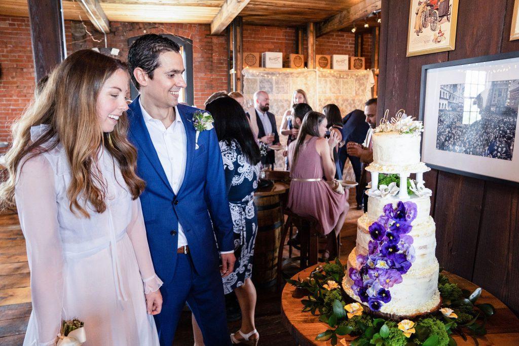 bride and groom admire wedding cake