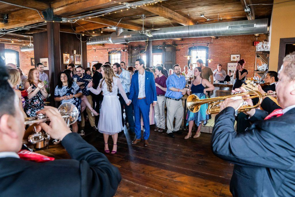 bride and groom greeted by mariachi band at wedding reception