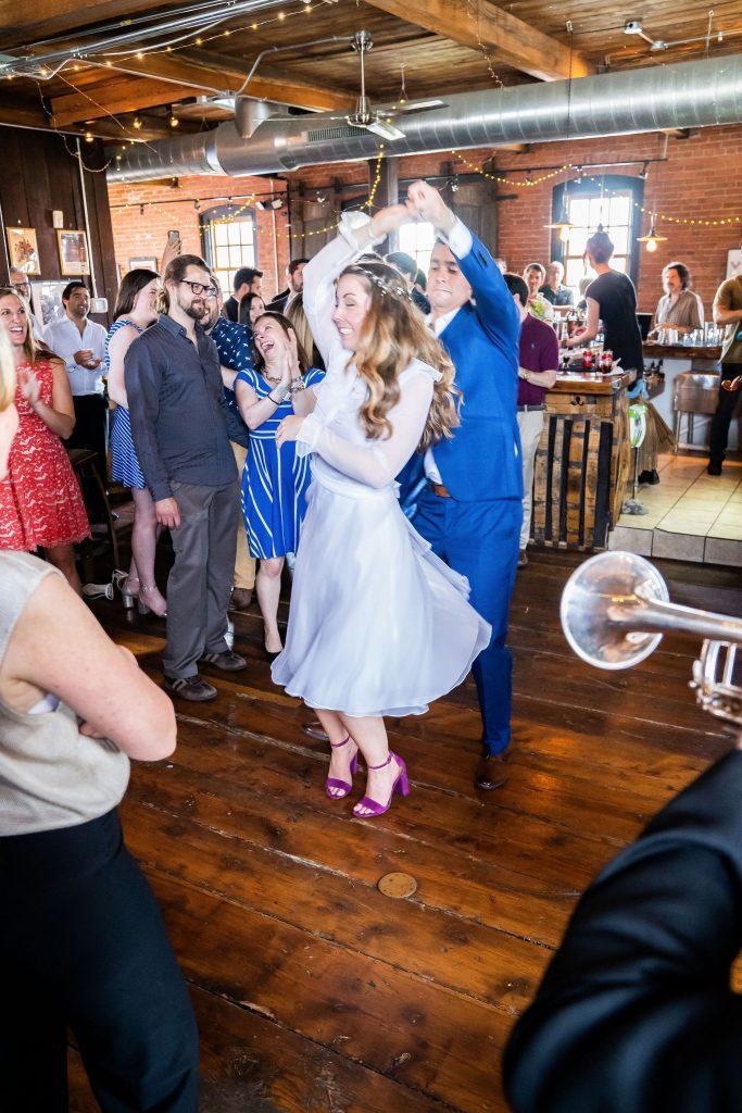 groom spins bride at wedding reception