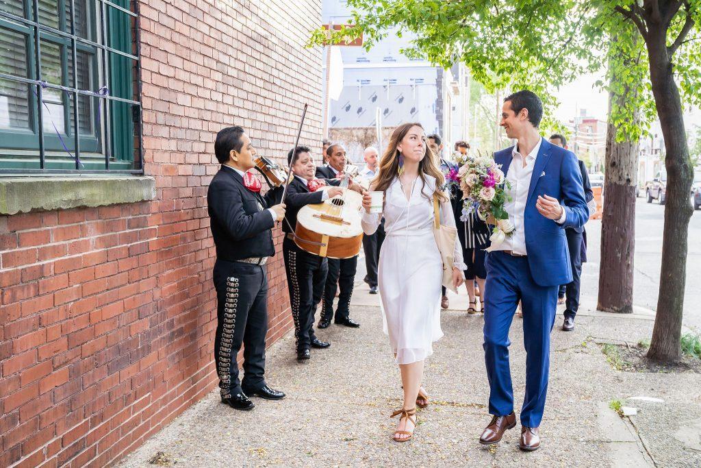 bride and groom walk with mariachi band in neighborhood