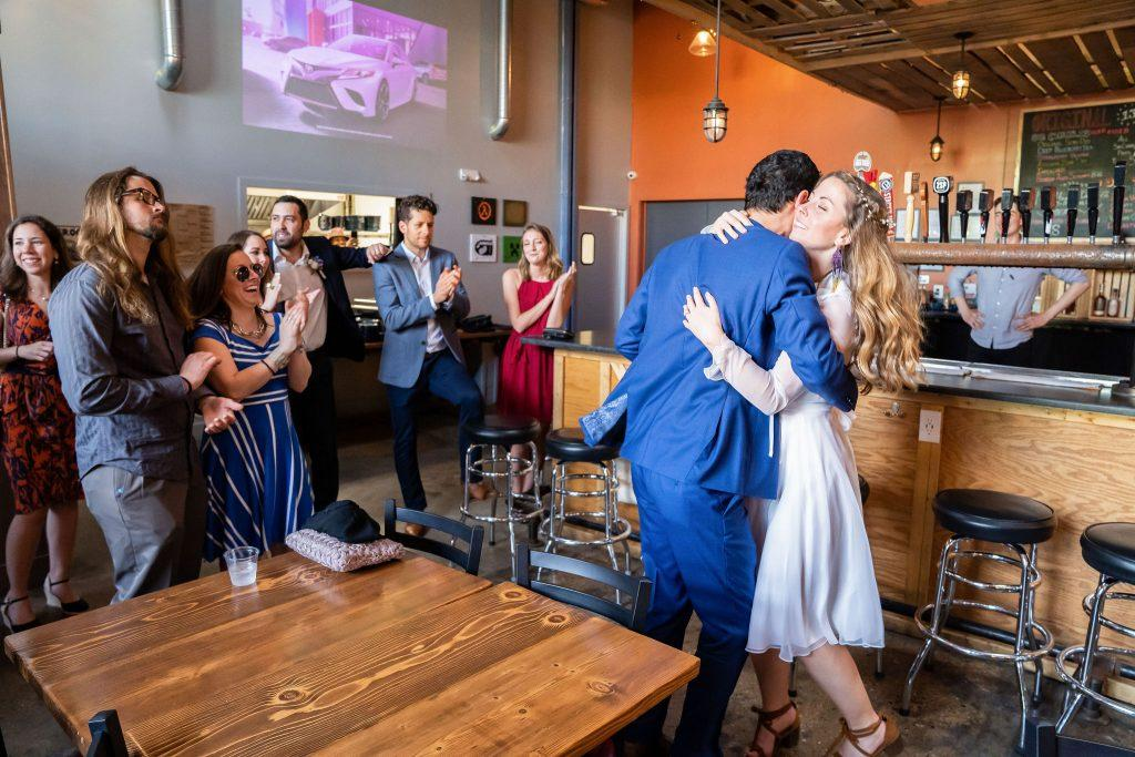 bride and groom dance at bar with friends