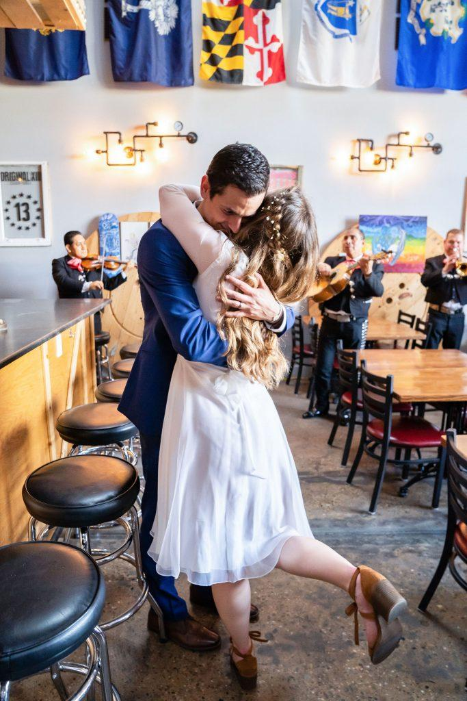groom embraces bride while dancing