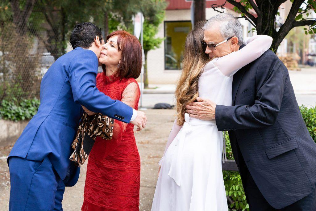 groom and bride hug parents