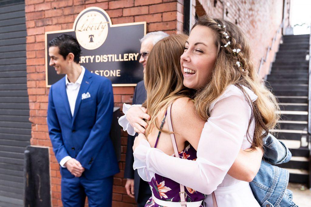 bride hugs bridesmais