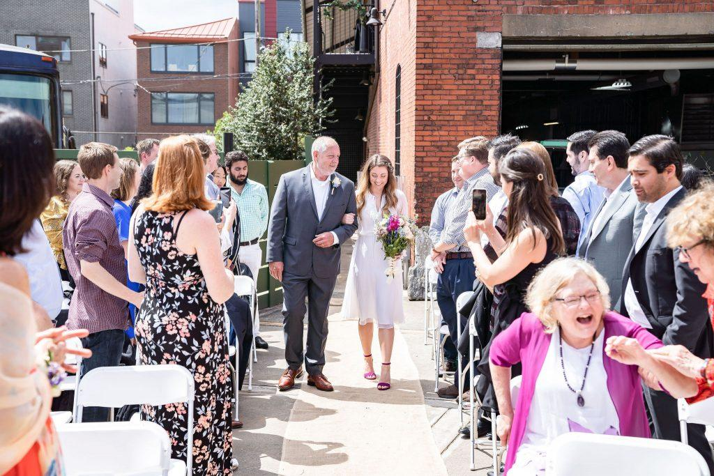 bride walks down aisle with father