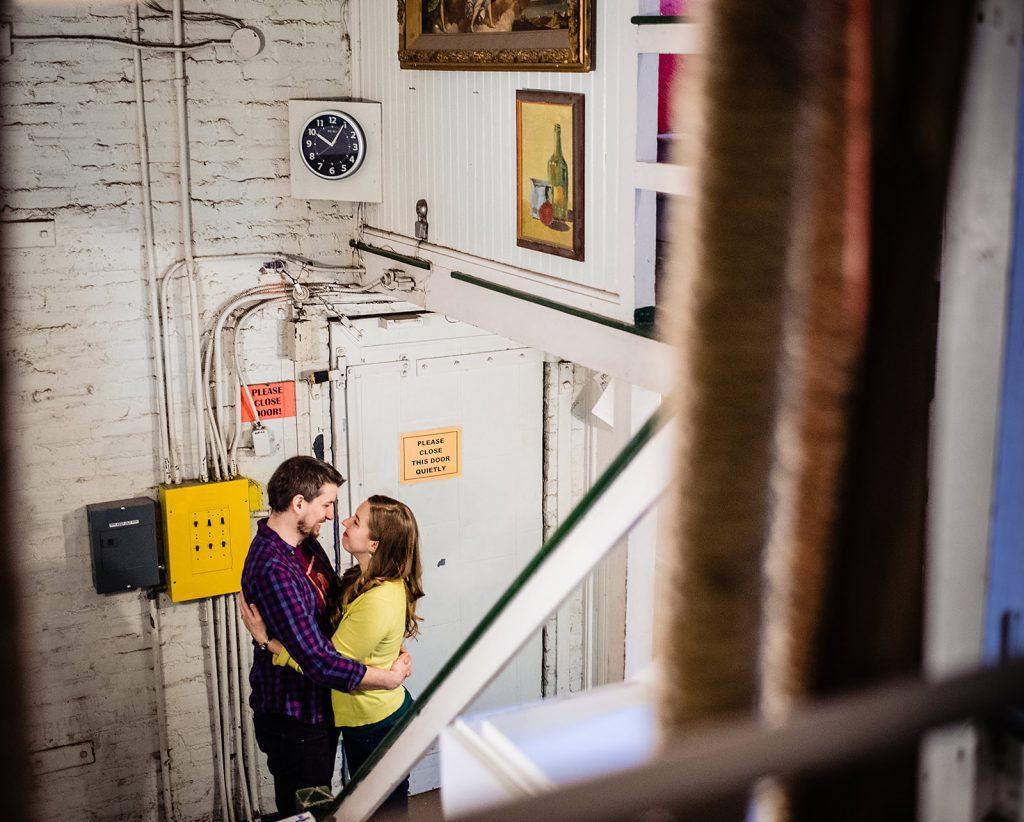 engaged couple embrace backstage