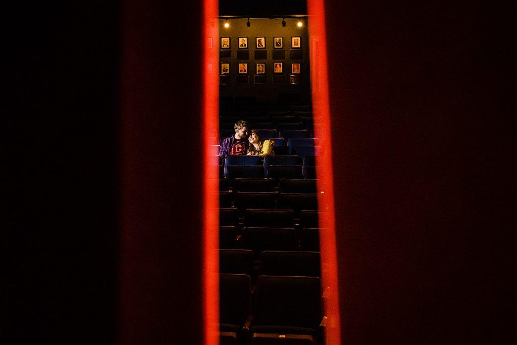 engaged couple sit in darkened theatre