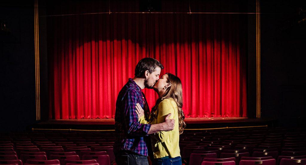 engaged couple kiss in front of stage