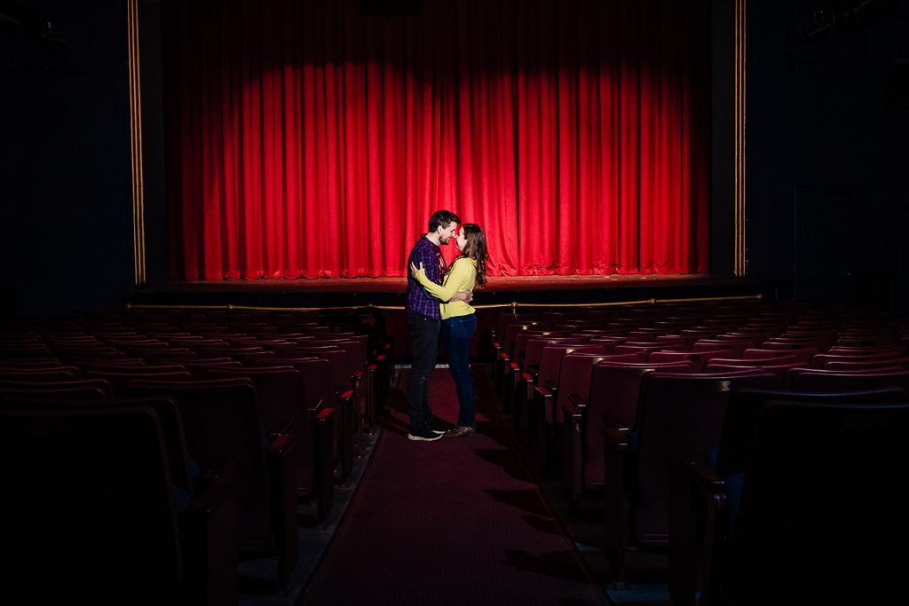 engaged couple kiss in center aisle of theater