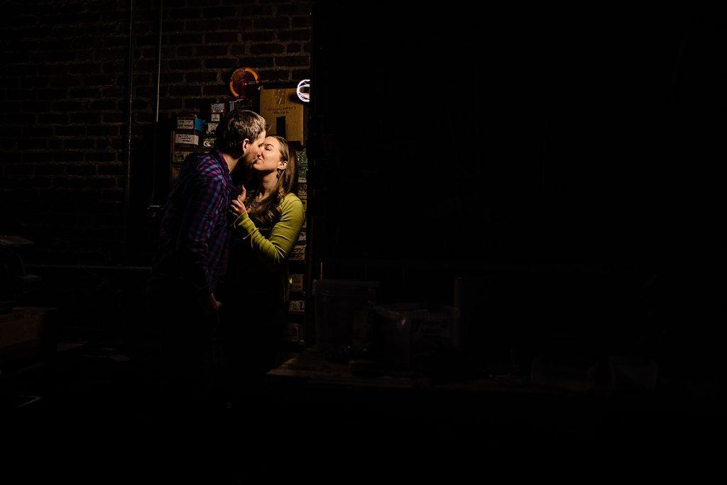 engaged couple kiss backstage in theatre