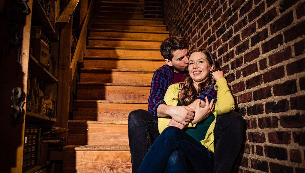 engaged couple embrace on steps backstage
