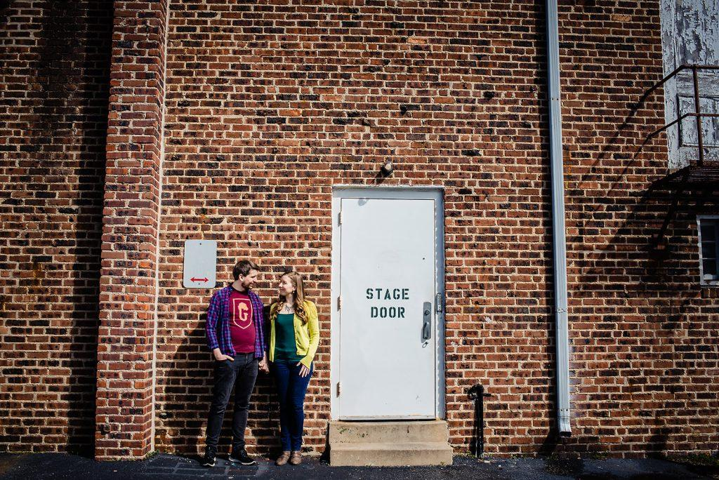 engaged couple pose at stage door entrance