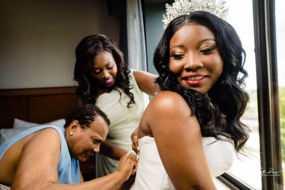 Mom and matron of honor assist bride with dress on wedding day