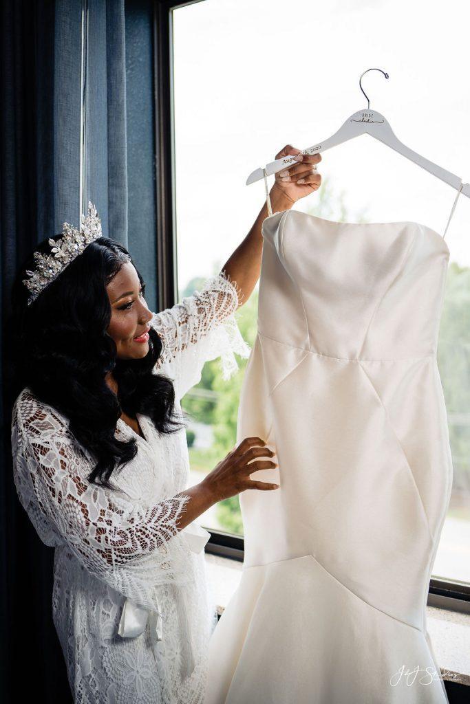 bride admires wedding gown