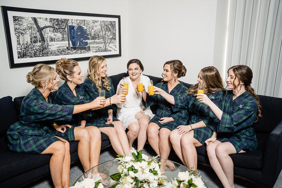 bride and bridal party toast in hotel room