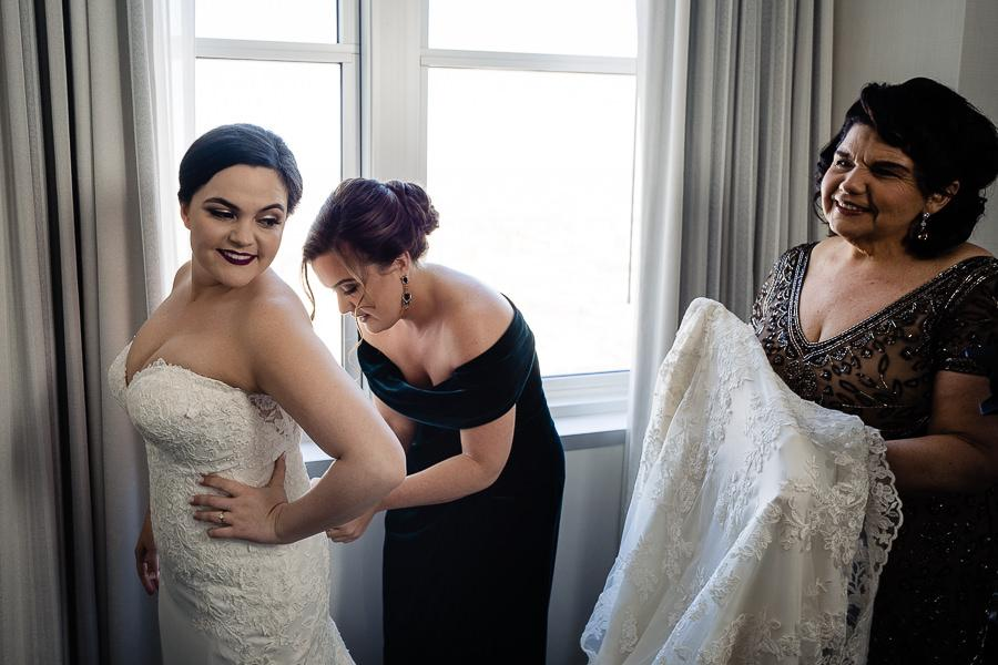 bride, mom and maid of honor help dress bride
