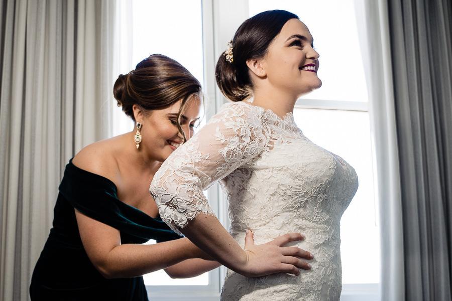 maid of honor helps bride into wedding dress