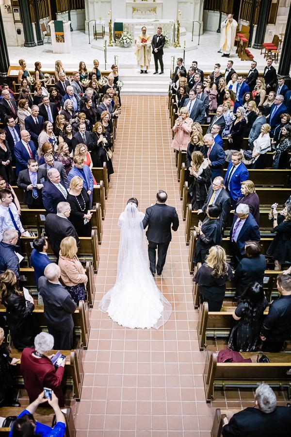 bride and father walk down cathedral
