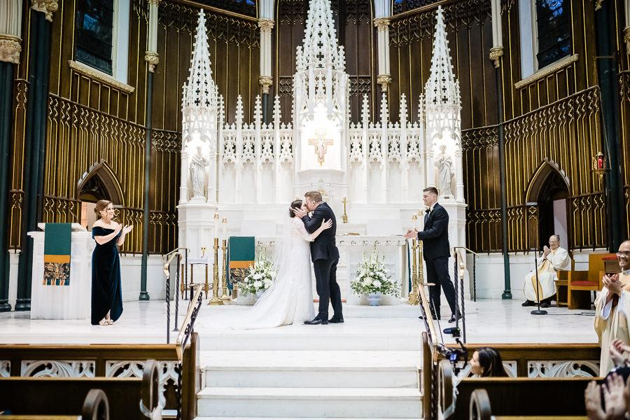 groom kisses bride in cathedral