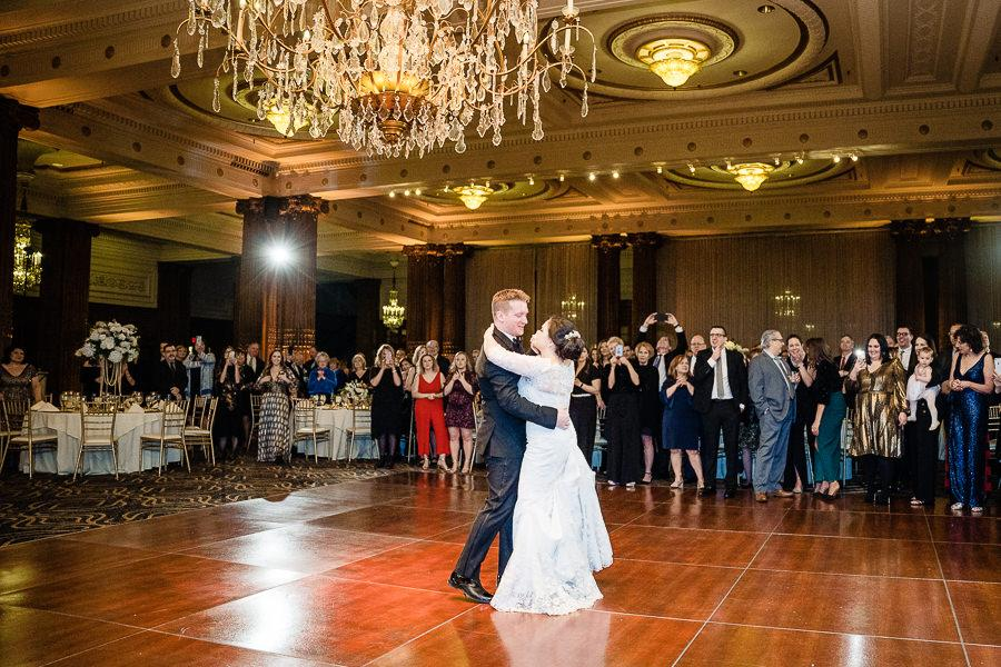 bride and groom first dance under chandelier