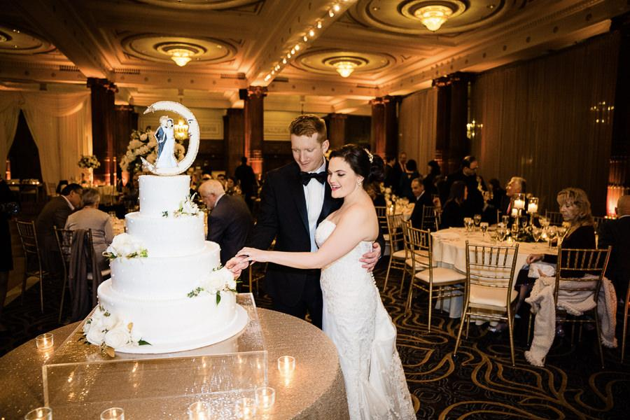 bride and groom cut 4-tiered white wedding cake