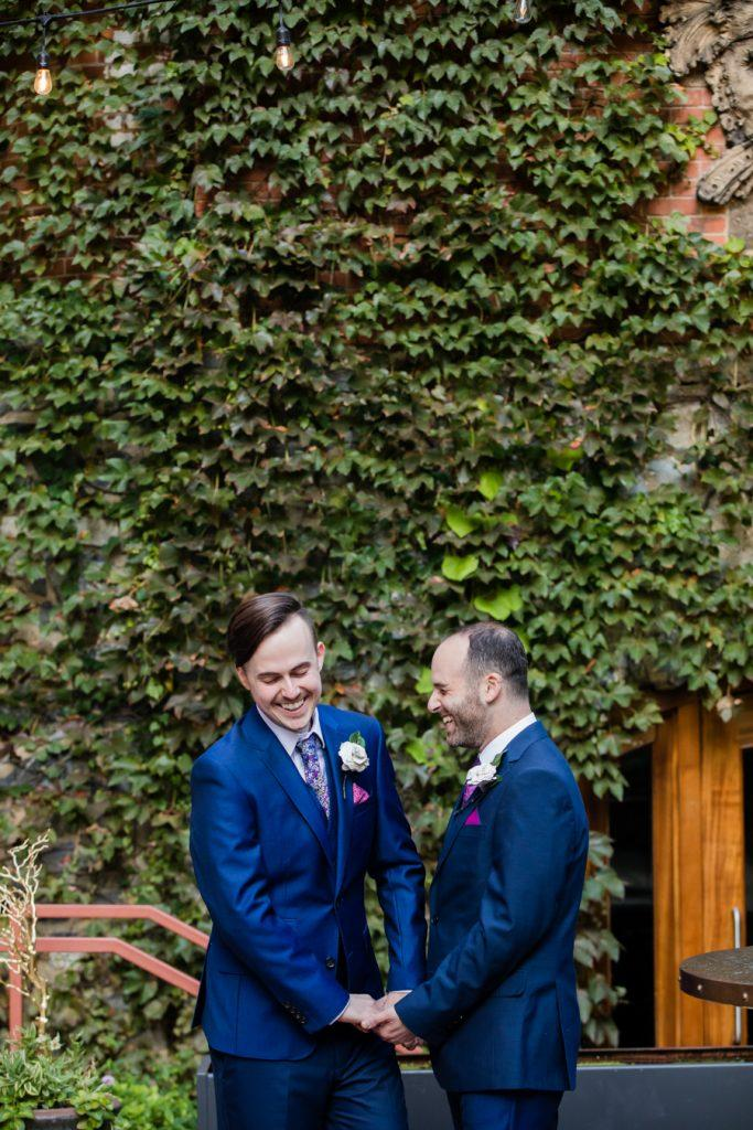 Philadelphia wedding photographers, the philatographer, two grooms holding hands in front of wall of green vines, lgbt