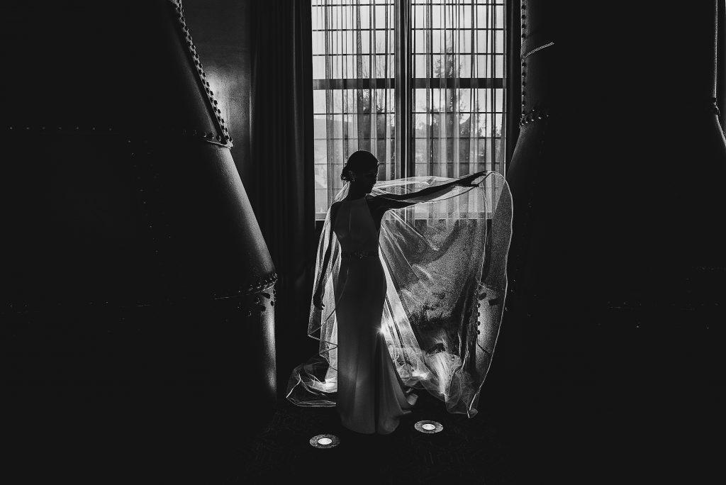 Philadelphia wedding photographers, kunda photography, black and white, bride standing in beam of light from window